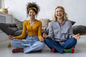 2 femmes en position du lotus en train de rire